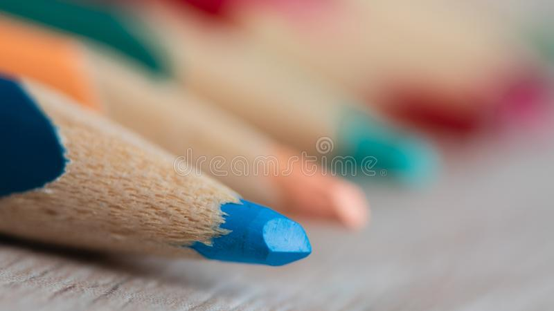 Closeup of wooden sharpened light blue pencil with the blurry other colored pencils stock photography