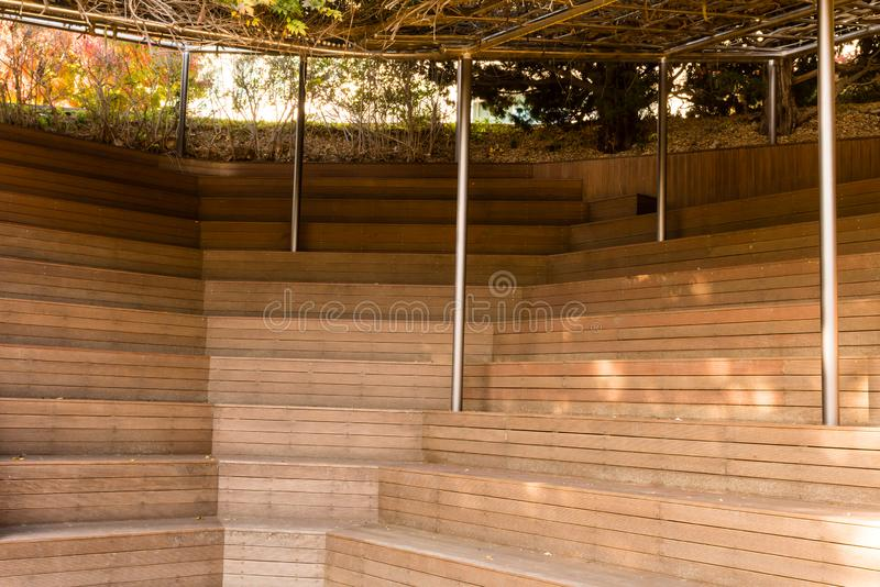 Closeup of wooden stadium seating. Shaded with tree branches on top of metal awning structure stock image