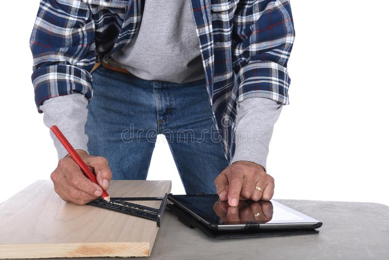 Closeup of a woodworker marking a cut line on a board as he checks specs on his tablet computer royalty free stock photo