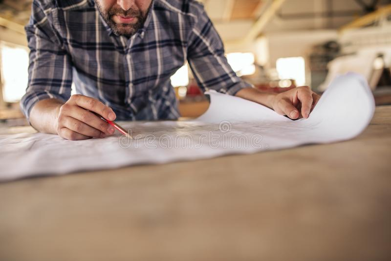 Woodworker leaning on a bench reading furniture design blueprints royalty free stock photography