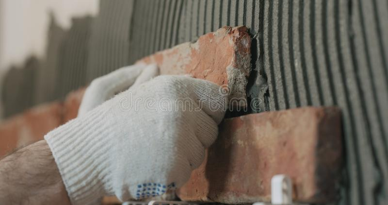 Closeup worker applying brick cuts tile to the wall stock photography