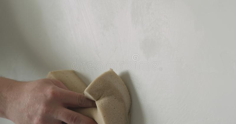 Closeup worker applying protective finish on a wall royalty free stock photo