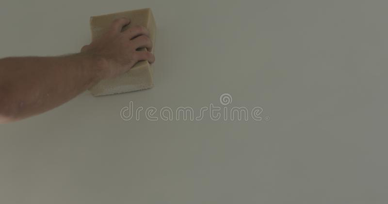 Closeup worker applying protective finish on a wall royalty free stock photos