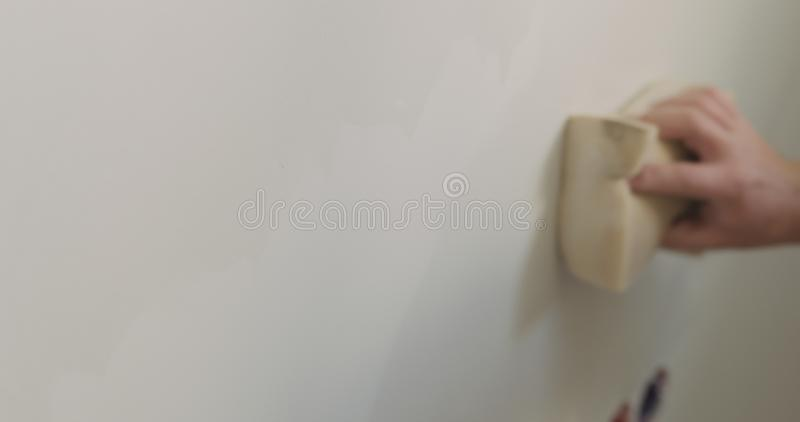 Closeup worker applying protective finish on a wall royalty free stock image