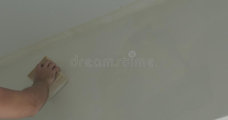 Closeup worker applying protective finish on a wall royalty free stock photography