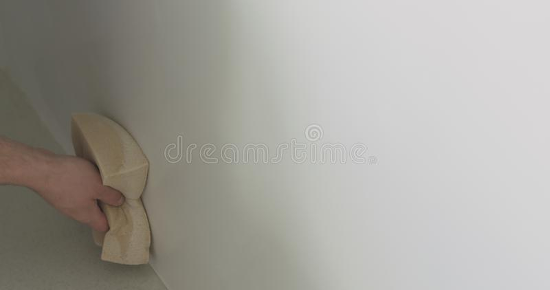 Closeup worker applying protective finish on a wall royalty free stock images