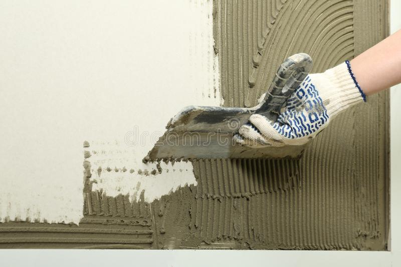 Closeup of worker spreading concrete on wall with spatula. Tile installation royalty free stock photos