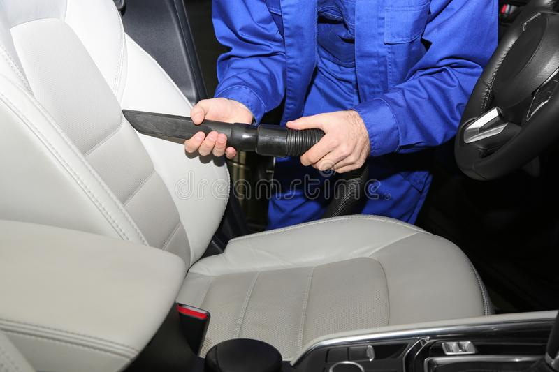 Closeup of worker vacuuming automobile seat. Car wash service stock photos