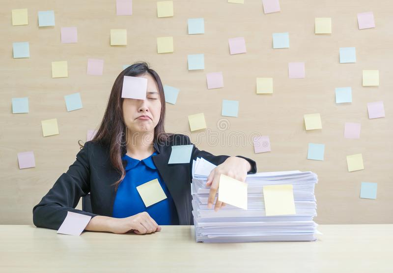 Closeup working woman are bored and tired from pile of work paper in front of her in hard work concept on blurred wooden desk and royalty free stock photos