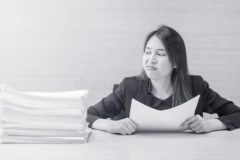 Closeup working woman are boring from pile of work paper in front of her in work concept on blurred wooden desk and wooden wall royalty free stock image