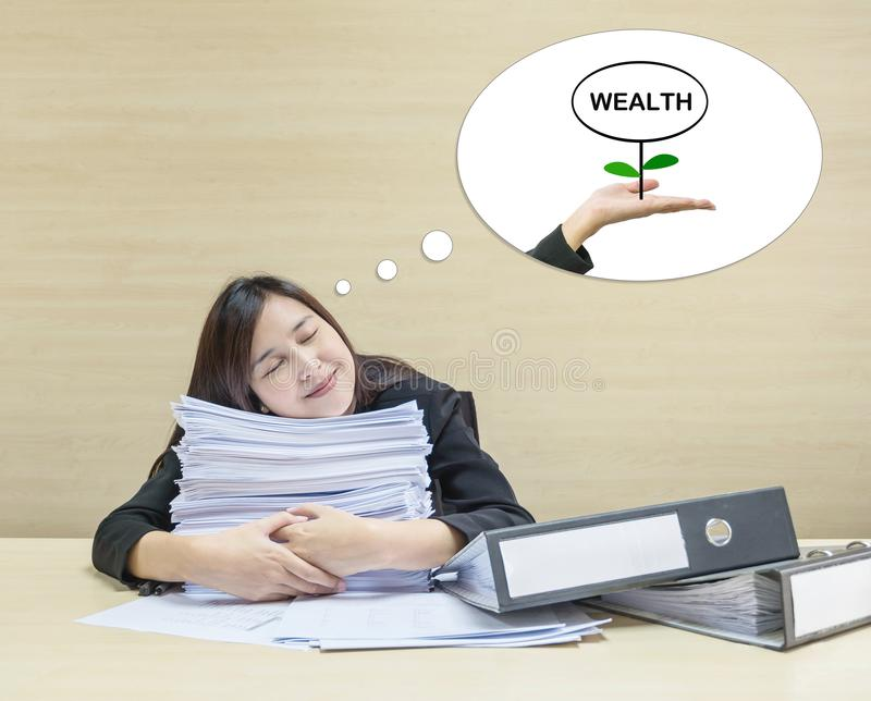 Closeup working woman sleeping with happy face with hug work paper in front of her and good dream to have wealth in future i royalty free stock images