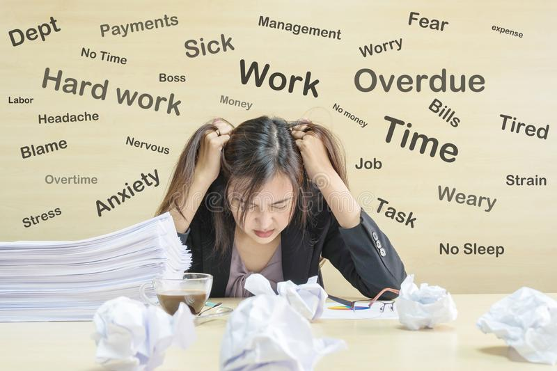 Closeup working woman are stressed from pile of work paper in front of her in work concept on wooden desk and wall textured stock image