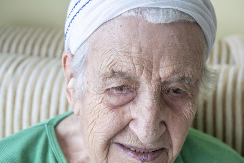 Closeup wrinkled face of a thoughtful senior woman royalty free stock photos