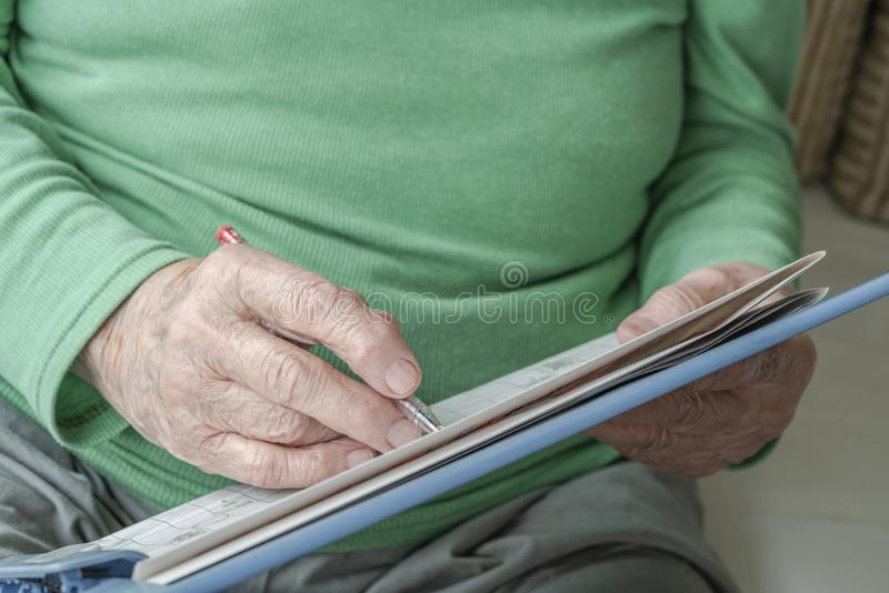 Closeup wrinkled hand of a senior person writing something stock image