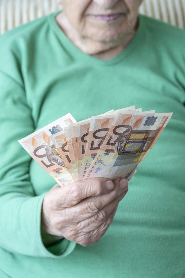 Wrinkled hand of a senior woman holding euro banknotes stock photography