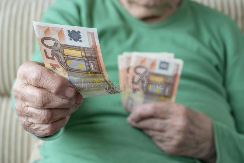 Wrinkled hand of a senior woman holding euro banknotes stock image