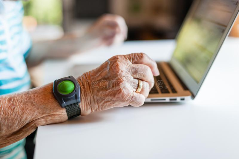 Closeup of wrinkled hand using a laptop stock photo