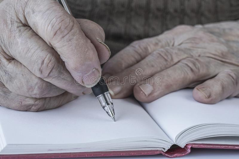 Closeup wrinkled hands of a person writing royalty free stock images