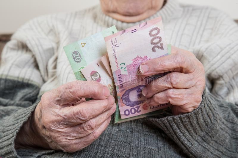 Closeup wrinkled hands of a senior person counting Ukrainian Hryvnia stock photo