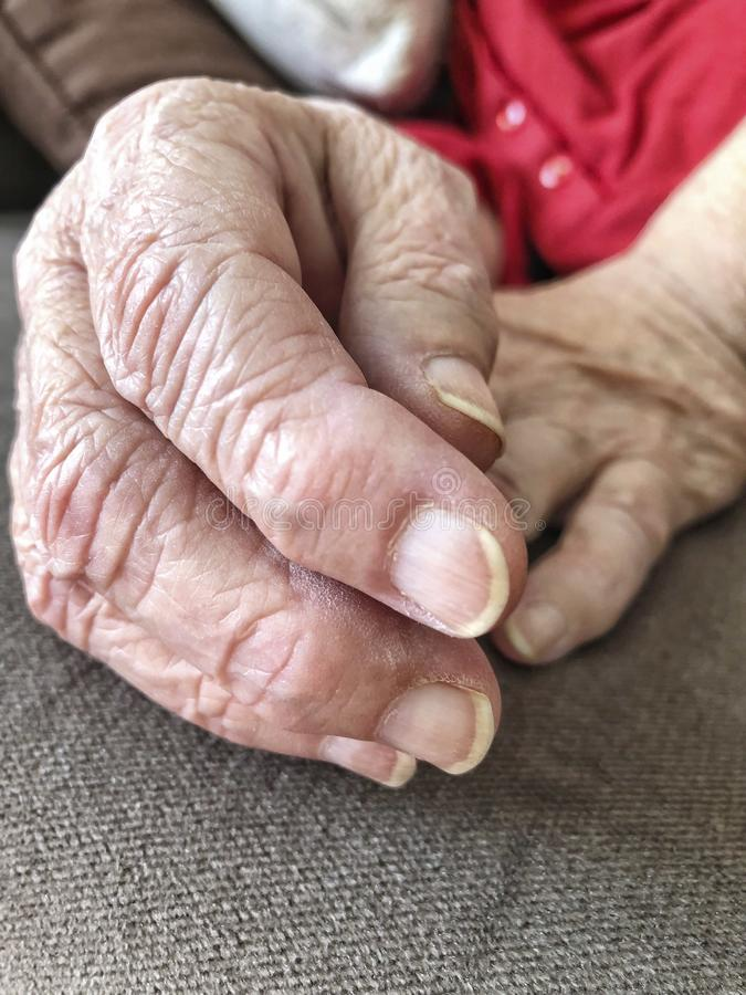 Closeup wrinkled hands of an old woman stock photos