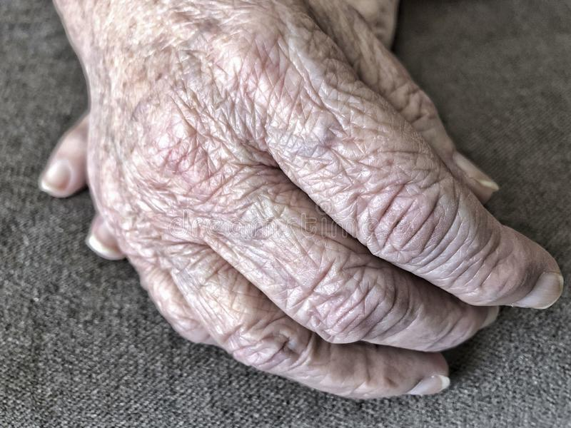 Closeup wrinkled hands of an old woman stock photography