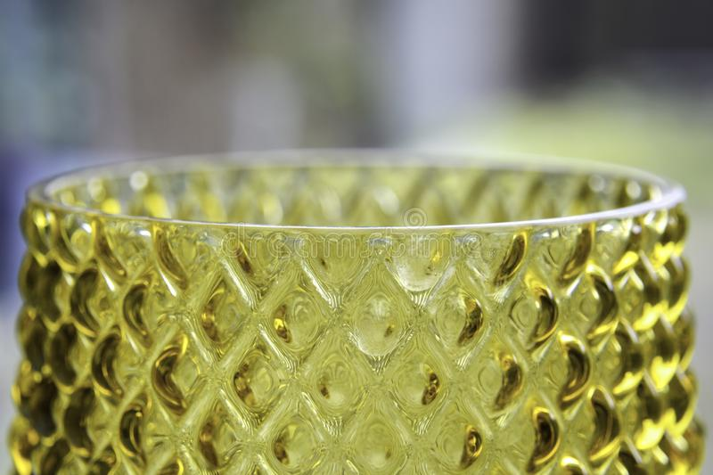 Closeup of a yellow glass vase texture surface. Blurry background. Interior decoration royalty free stock photo