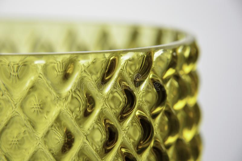 Closeup of a yellow glass vase texture surface. White background. Interior decoration royalty free stock image