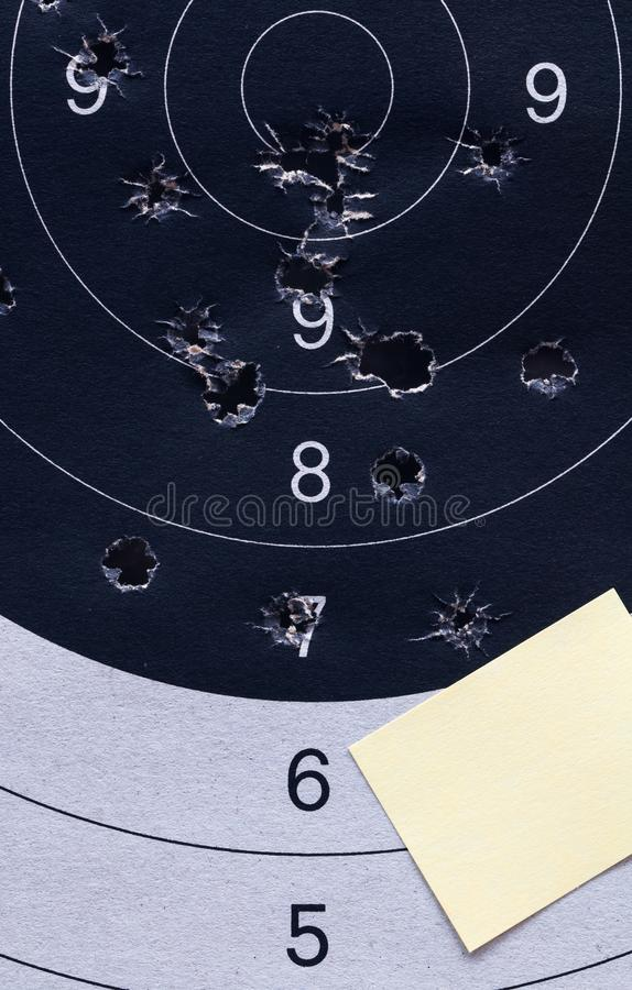Closeup yellow note papers sheet. On black and white a shooting paper target and bulls eye with bullet holes. royalty free stock image