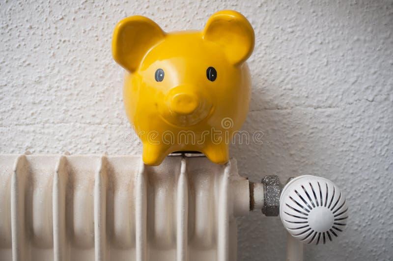 Yellow piggy bank on radiator - energy savings concep. Closeup of yellow piggy bank on radiator - energy savings concept stock images