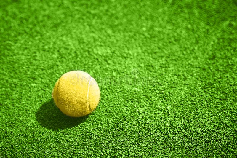 Closeup of a yellow tennis ball. Closeup of a yellow tennis ball on a green synthetic court royalty free stock images