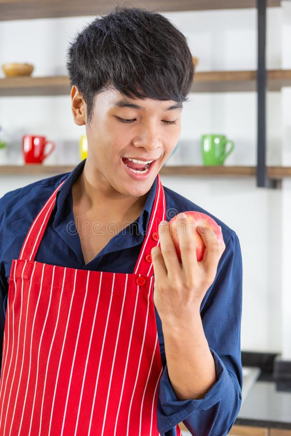 Closeup of young asian man with apron biting red apple royalty free stock photos