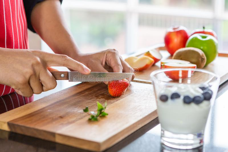 Closeup of young asian man with apron cutting strawberry red and green apple kiwi orange on wooden board royalty free stock photos