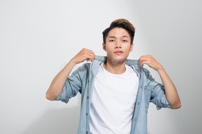 Closeup of a young Asian man holding his hands on the collar of his jeans shirt isolated on a white background.  royalty free stock photography