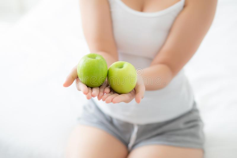 Closeup young asian woman holding and eating green apple fruit in the bedroom at home. Lifestyle of nutrition girl healthy and care weight loss, health and royalty free stock image