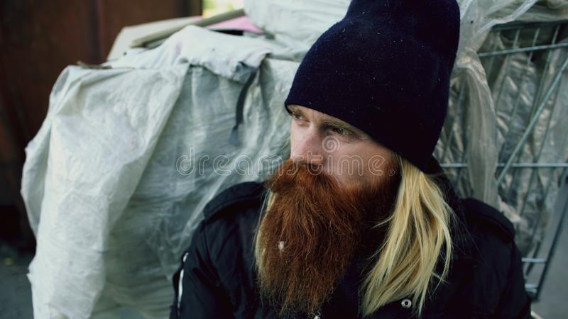 Closeup of young bearded homeless man sitting near shopping cart upet and stressed alone in the street royalty free stock photos