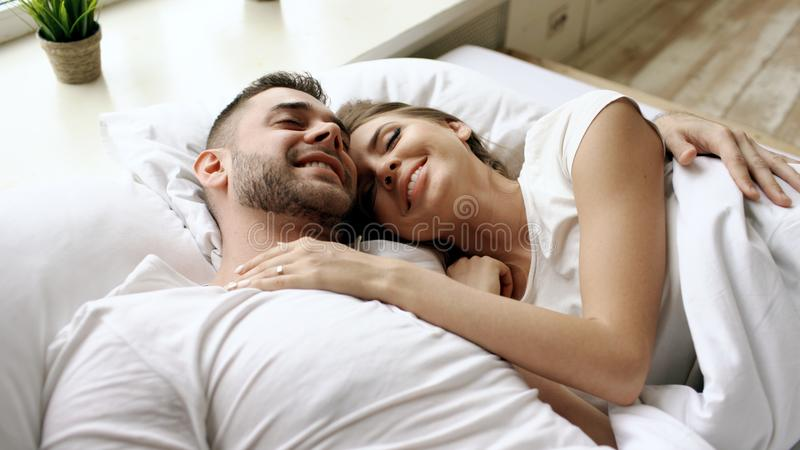 Closeup of young beautiful and loving couple talk and hug into bed while waking up in the morning. stock photos
