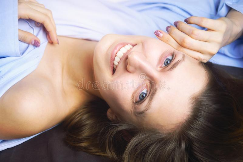 Closeup of young beautiful smiling woman in blue lying in bed. Natural beauty. stock photos