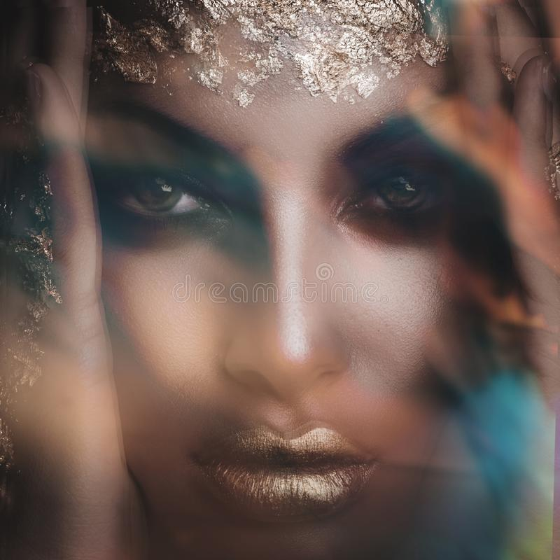Closeup of young black woman face with golden lips and makeup  intentionally blurred royalty free stock image