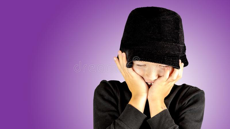 closeup of young boy in black shirt and black hat with shy expression stock image
