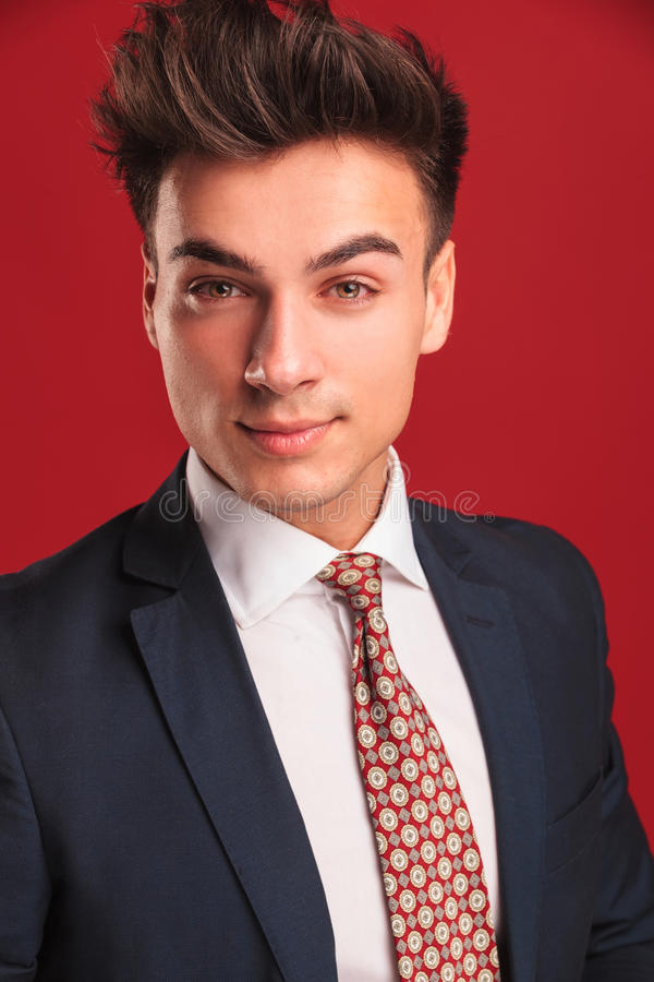 Closeup young businessman in black suit with red tie royalty free stock image