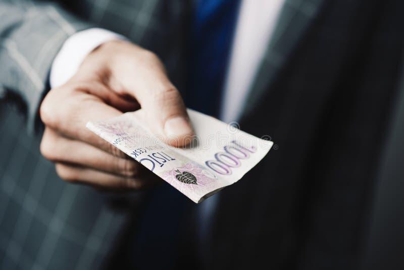 Businessman giving a 1000 czech korunas banknote royalty free stock photography
