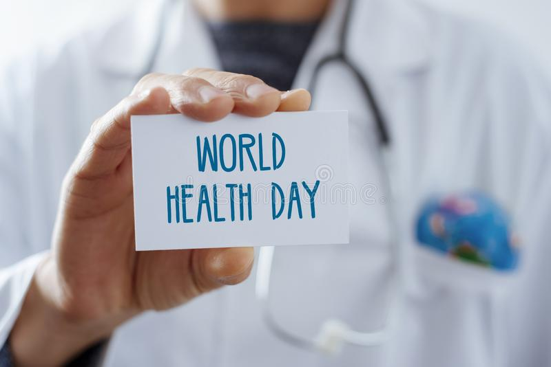 Doctor with signboard with text world health day. Closeup of a young caucasian doctor man, with a world globe in the pocket of his white coat, showing a royalty free stock photos