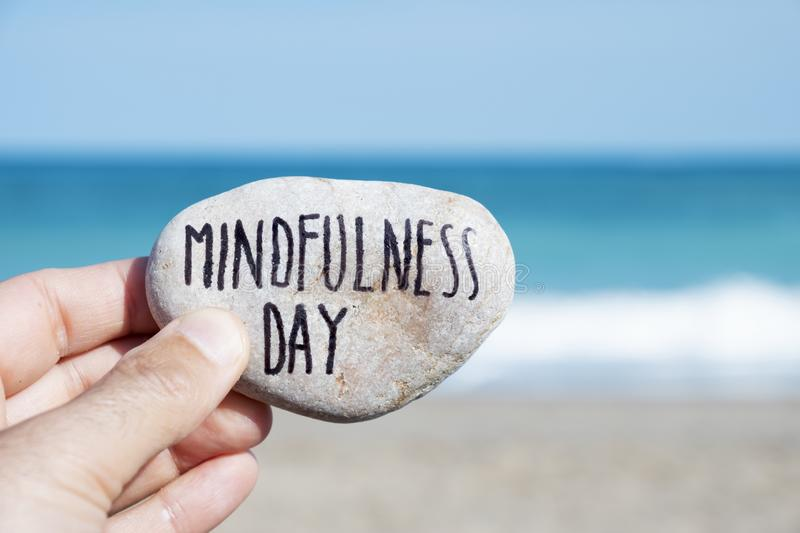 Man on the beach and text mindfulness day stock photos