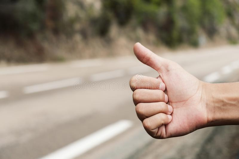 Young man hitchhiking on a secondary road. Closeup of a young caucasian man hitchhiking standing on the roadside of a secondary road, with his thumb up royalty free stock photos