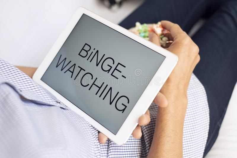 Man and tablet, with the text binge-watching in it. Closeup of a young caucasian man lying comfortably on a couch, eating popcorn while is watching his tablet stock photography
