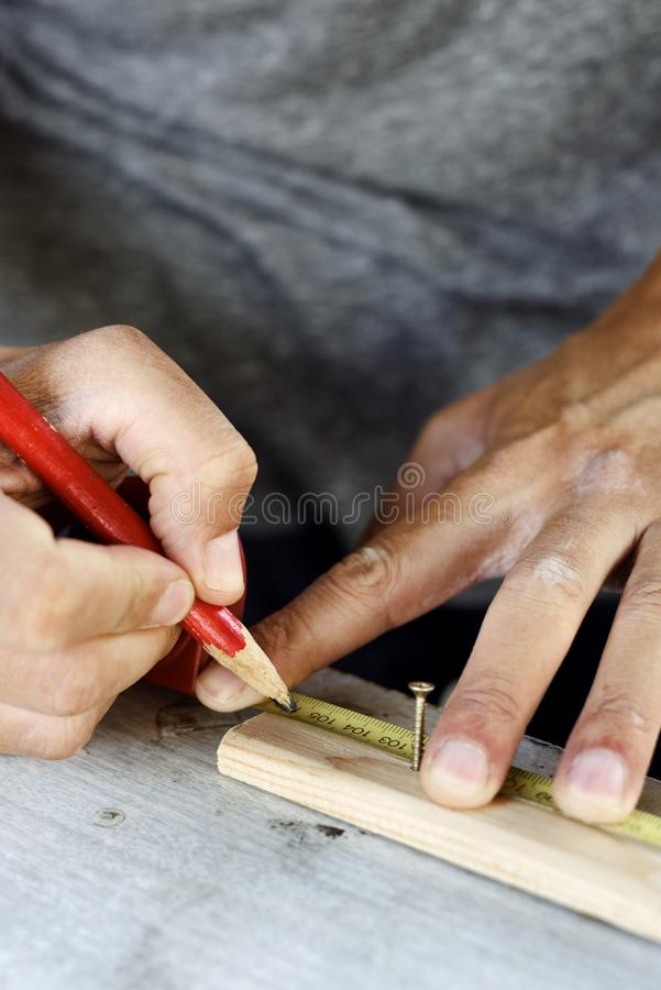 Young man making a mark in a wood strip royalty free stock images