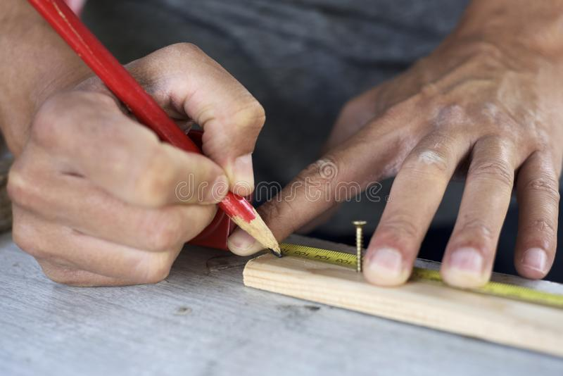 Young man making a mark in a wood strip stock photo
