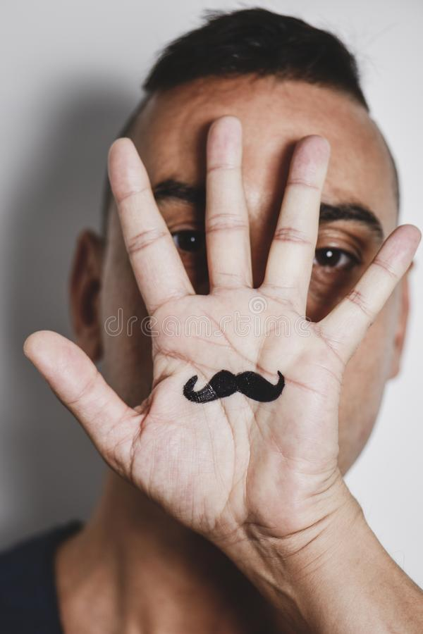Man with a mustache painted in his palm. Closeup of a young caucasian man with the palm of his hand in front of his face, with a mustache drawn in it stock photos