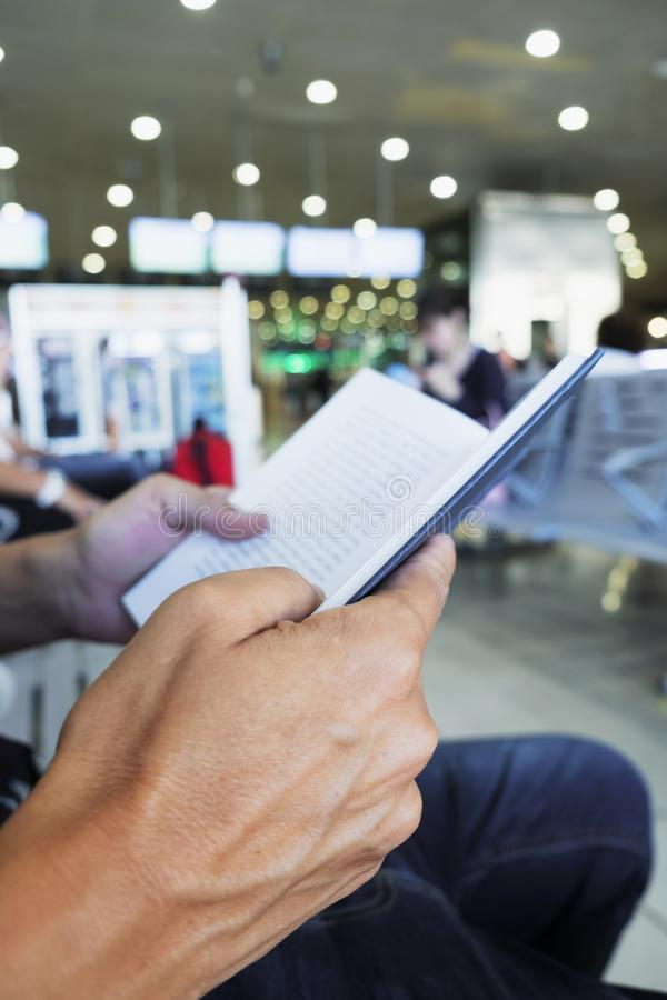 Man reading a book in a station or airport stock photos