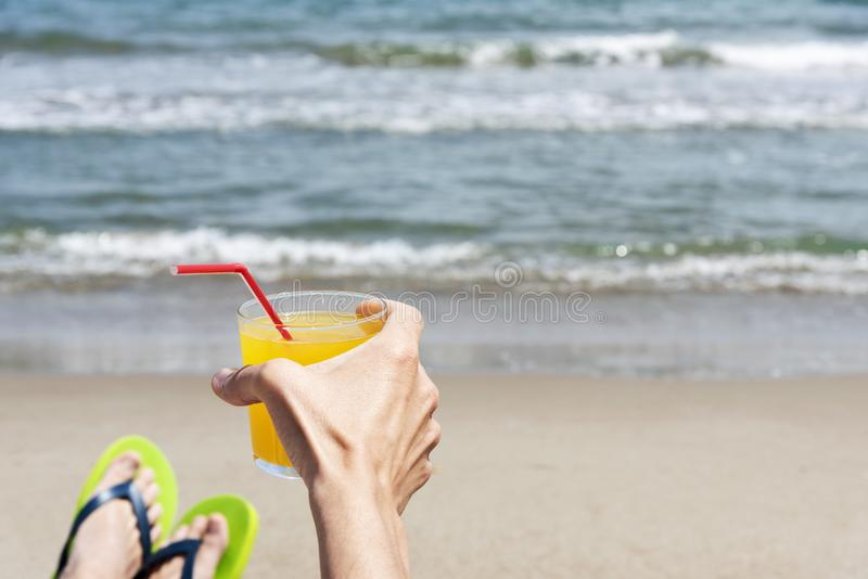 Young man relaxing on the beach. Closeup of a young caucasian man relaxing on the beach, wearing a pair of green flip-flops, with a glass with a refreshing royalty free stock image